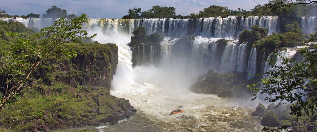 view of the Iguazu Falls and boats with tourists